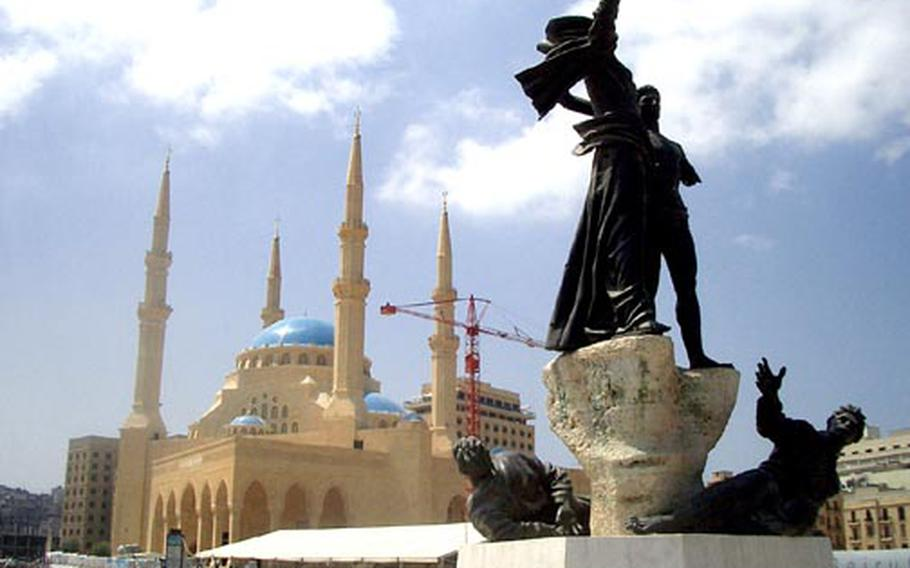 A bullet-riddled monument to the so-called martyrs of Lebanon's Civil War stands in front of the new mosque being built in downtown Beirut.