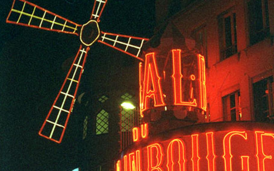 The infamous Moulin Rouge cabaret in the Pigalle district of Paris lights up the night with its neon signs.