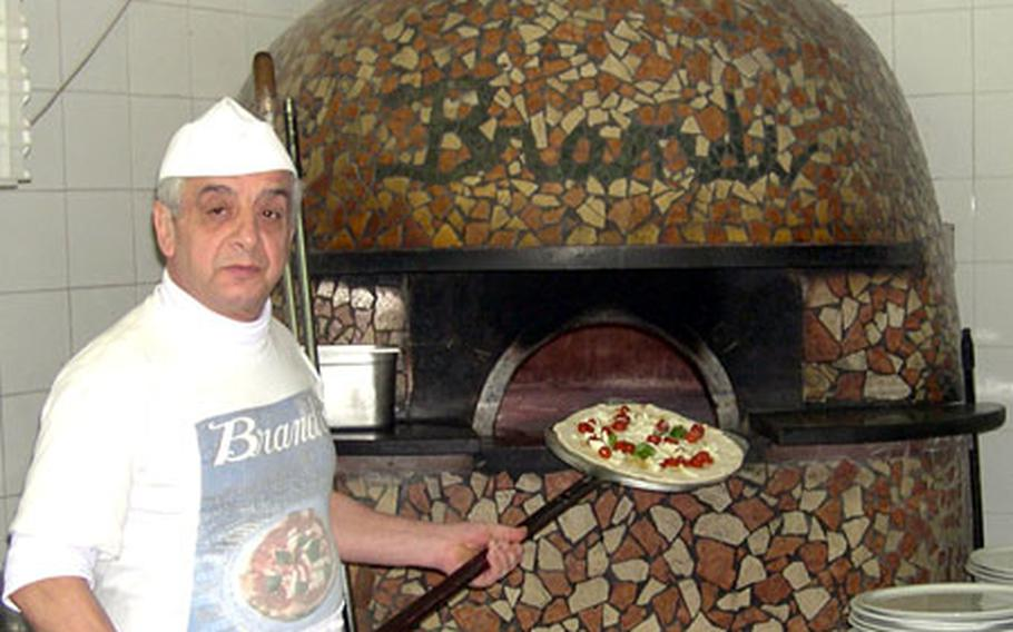 A chef prepares to put another pizza in one of the two ovens at the Brandi Pizzeria. The restaurant, where the Margherita pizza was named, has been in the same location since 1790.