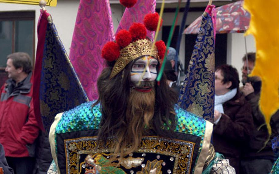 A highly decorated warrior stalks the main street during the celebration.