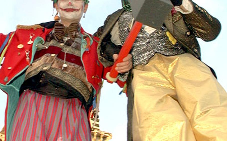 Carnivale participants dressed as clowns tower above the crowded streets of Aci Reale, Sicily, during Carnivale. Part of the tradition is to hit other partygoers on the head with toy hammers.