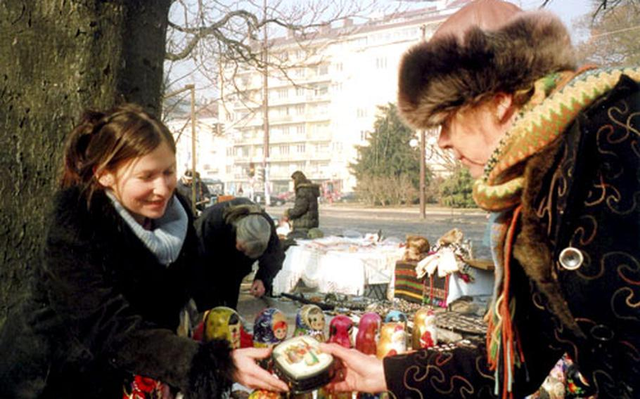 Maria Tracheva, left, shows tourist a Russian lacquered box. She and her husband are both biology teachers, but they also sell Russian souvenirs on the street to make enough money for themselves and their three small children.