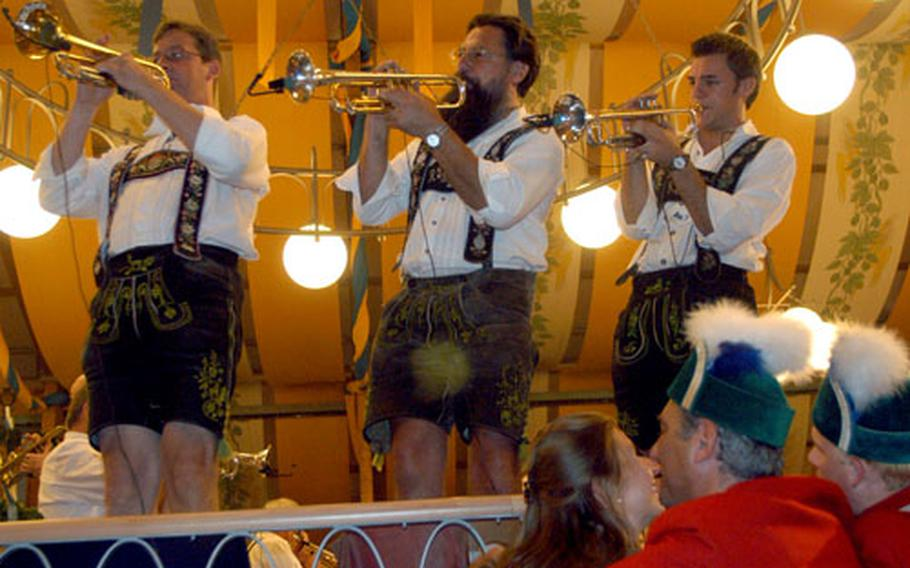 A couple steals a smooch as a band plays inside one of the 14 beer tents during the 2005 Oktoberfest in Munich, Germany.