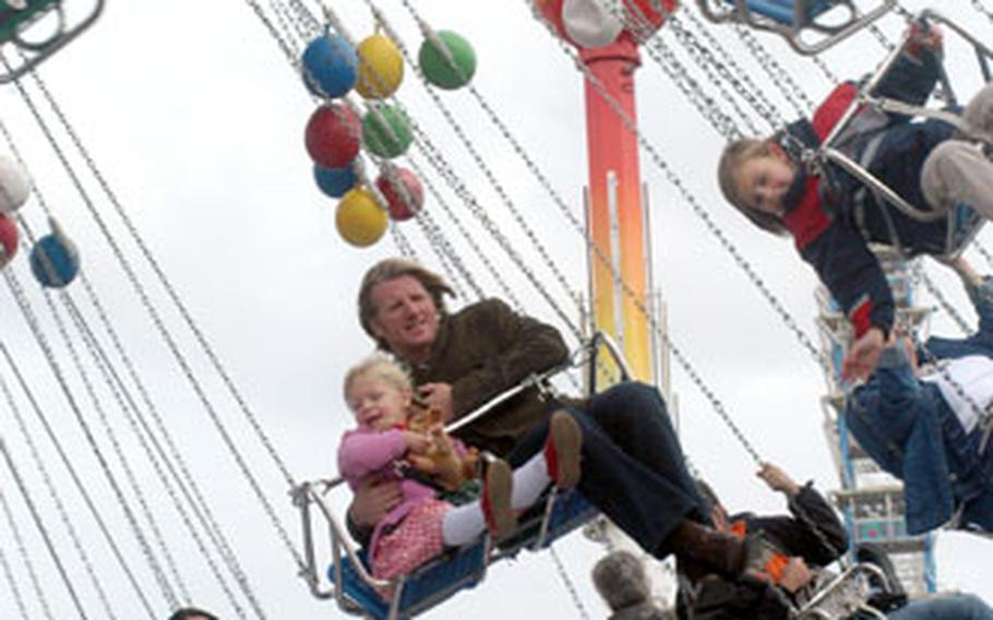 A father and daughter take a whirl on the swings at the 2005 Oktoberfest in Munich, Germany.