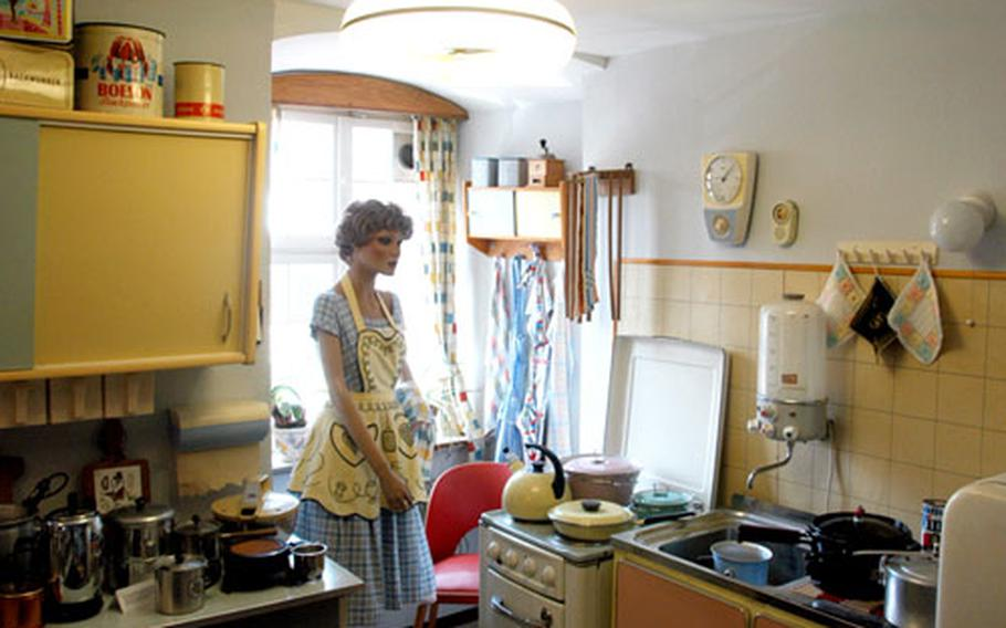 A mannequin dressed as a typical German housewife stands in her pastel-colored kitchen.