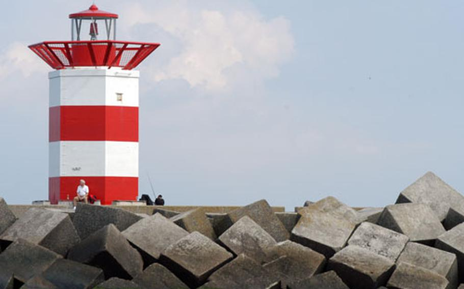 A lighthouse marks the entrance to the port at Scheveningen, Netherlands. Until about 200 years ago, Scheveningen was a small fishing village. Now it is the most popular seaside resort in Holland.