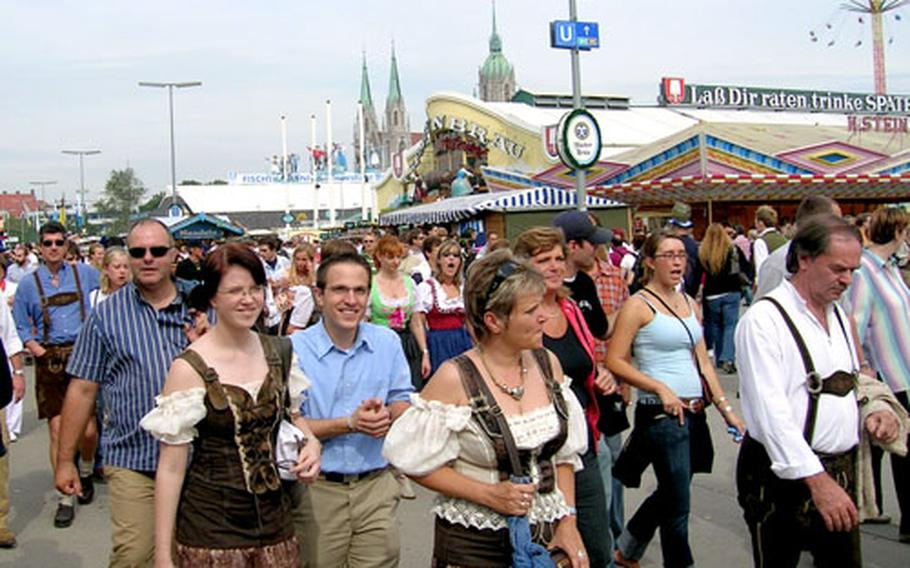 Patrons, some dressed in Bavarian finery, wander between beer tents looking to claim a seat on the opening day of this year's Oktoberfest.