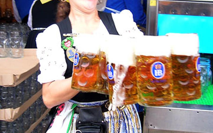 A waitress rushes several one-liter mugs of beer from the serving area to eager patrons on the opening day of the this year's Oktoberfest.