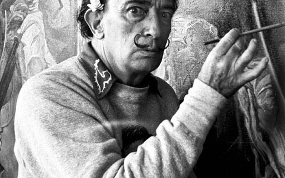 Salvador Dali poses for Stars and Stripes photographer Gus Schuettler, who spent a day with the artist and his wife at Cadaqués, Spain, in 1962.