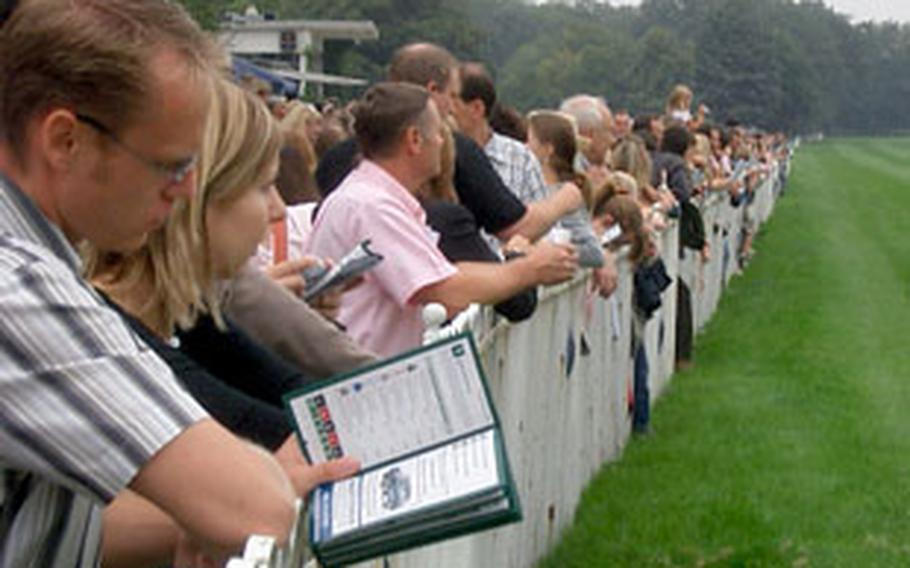 Patrons gather along the rail as they wait for another race to begin at the Galopprennbahn Frankfurt.