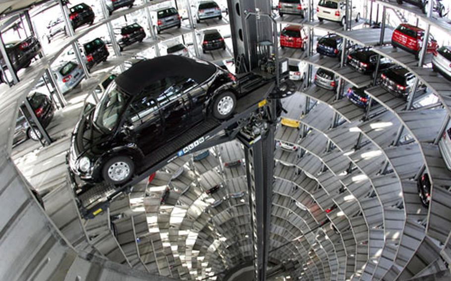 Completed cars are stored in huge glass towers in Autostadt near the factory where they were made. When it is time to be delivered to their owners, they are lowered to the ground via a large robotic arm and conveyor belts.