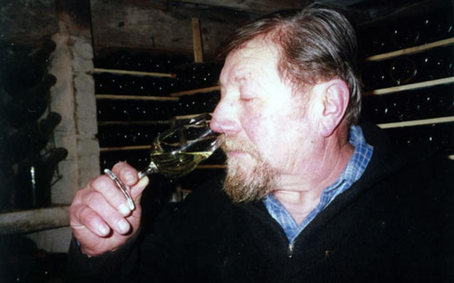 """Lucien """"Bacchus"""" Aviet tests the nose of one of his Jura wines. He produces 25,000 bottles of wine per year, a mixture of white and red."""