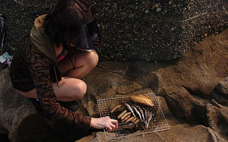 A Japanese woman cooks fish on the reef of Monkey Island off of a homemade grill. During the summer months many patrons are invited to participate in activities on the island.