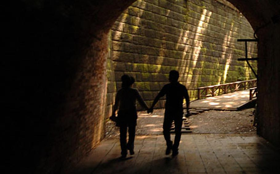 A Japanese couple holds hands as they visit the many historical remains on Monkey Island.