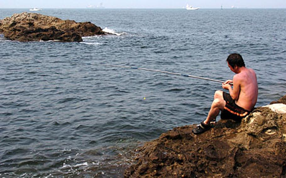 A Japanese man fishes off the reef of Monkey Island.
