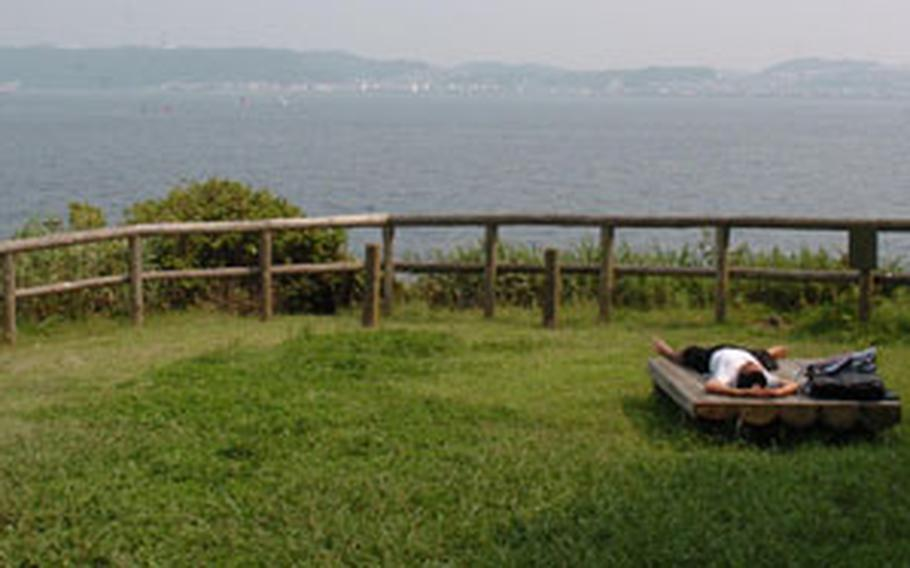 A Japanese man stretches out on a bench during a hot summer day on Monkey Island.
