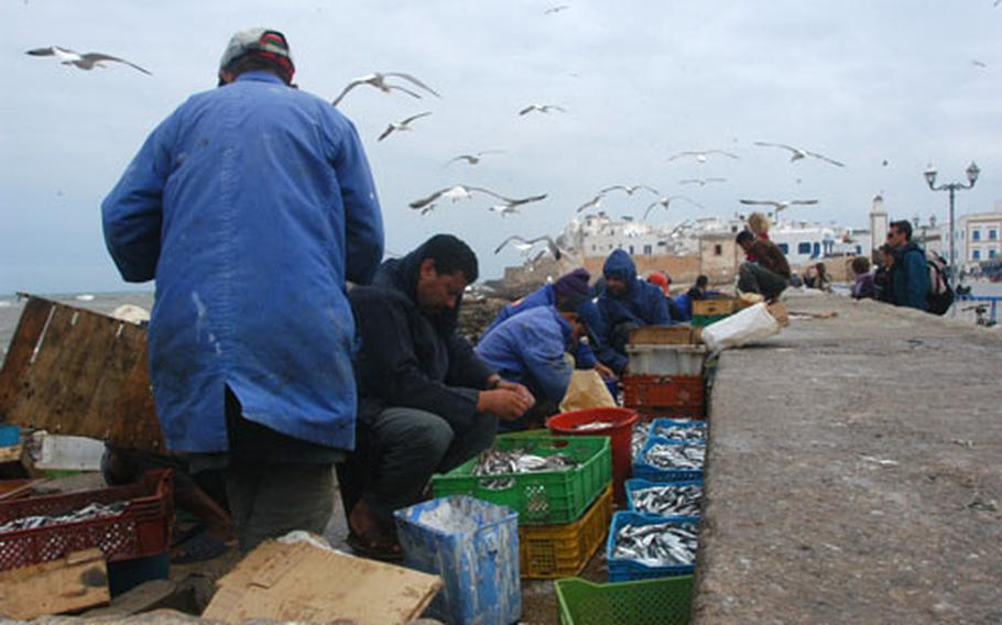 Men clean sardines and other fish near the docks in Essaouira, a fishing port on the Atlantic coast of Morocco.