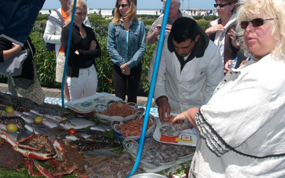 A woman orders some fish from one of the seaside vendors in Essaouira. Essaouira is about 80 miles north of Agadir.