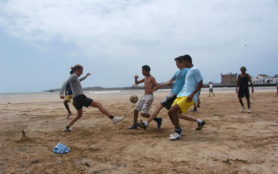 A group of youn men play soccer on the beach in Essaouira. The spacious beach has lots of room for sports and relaxing.