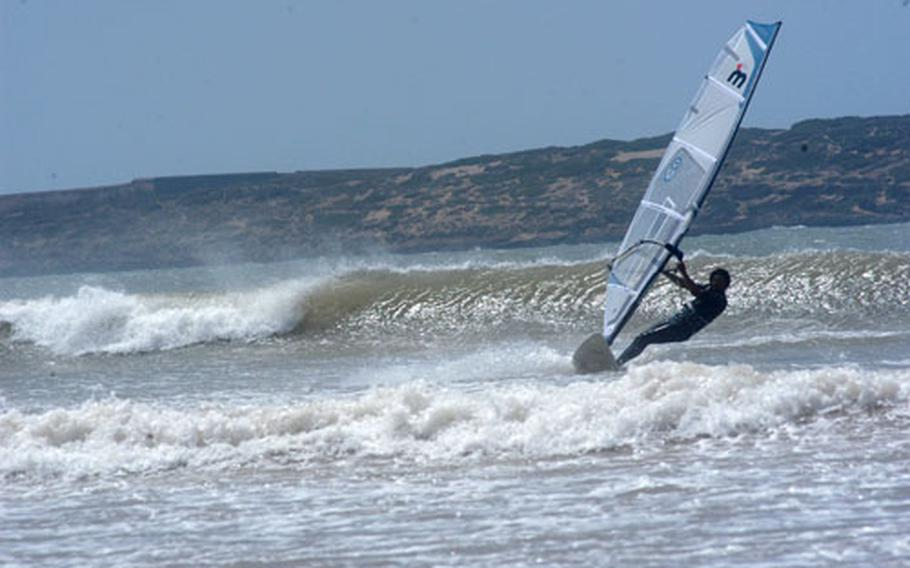 A windsurfer rides the waves in the bay of Essaouira. With its windy weather and wide beach, Essaouira is a favored destination of windsurfers.