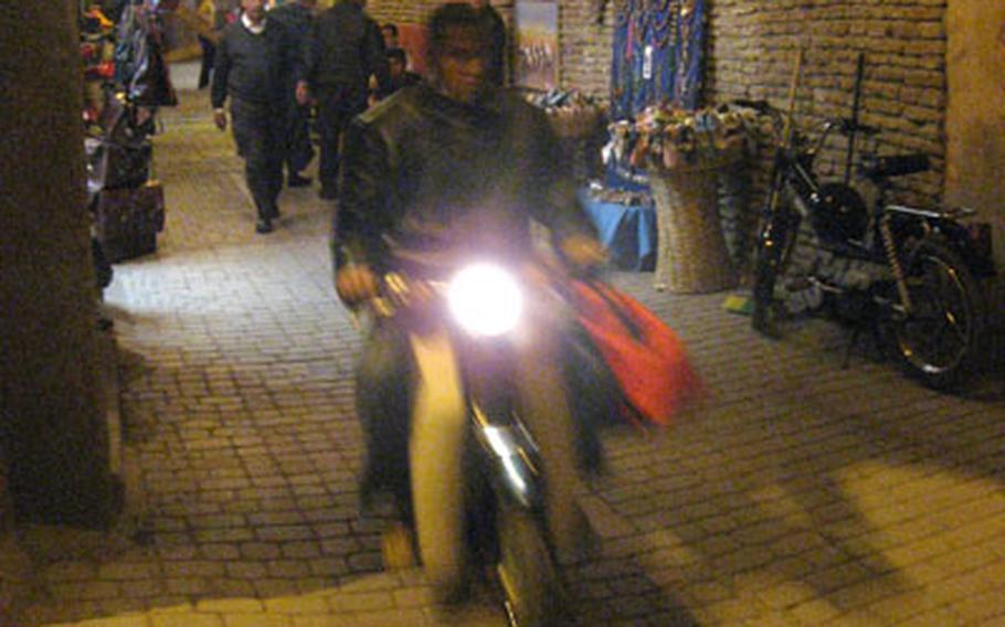 Traveling at night aboard a scooter through the medina of Marrakech, Morocco, is a different way to get some sightseeing done.