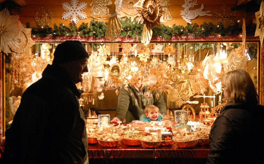The child of one of the vendors at the 2006 Bad Hersfeld Christmas market is full of holiday cheers as shoppers pass by the stand.