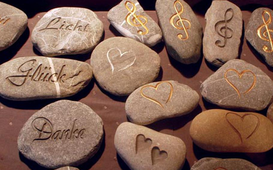 Stones chiseled with messages are sold as paperweights. The stones' messages at left read, from top to bottom: light, luck and thanks.