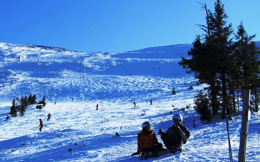 Skiers take a break for photos on the wide open slopes in Jasná.