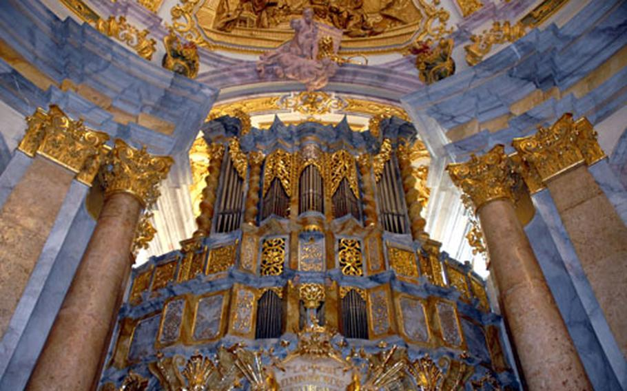 The chapel organ is flanked by pillars and surrounded by statues and paintings. In typical baroque fashion, the church's interior is highly decorated.
