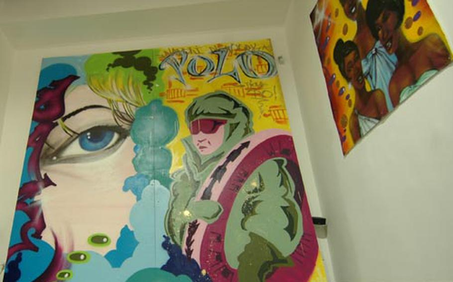 """A collaboration between New York City artist Daze and Naples artist Polo is on display as part of the """"South Bronx to Naples"""" art display at the Entropy Art In Progress gallery in downtown Naples. To the right is another Daze work titled """"Martha Reeves and the Vandellas."""""""