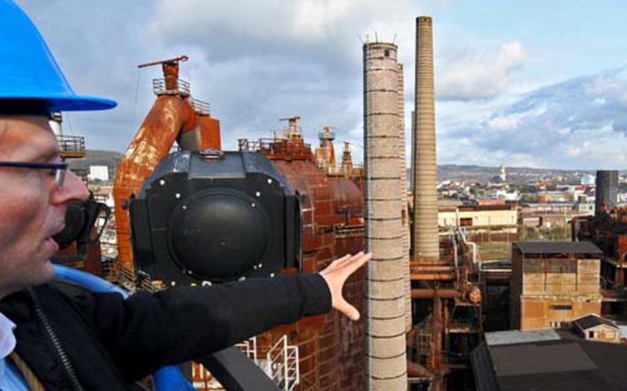 Hanns-Wilhelm Grobe, spokesman for the Völklinger Hütte in a former ironworks center, explains details of the furnace system on top of his workplace. The city of Völklingen, Germany, is in the distance.