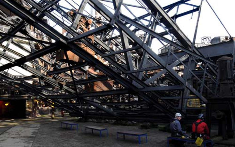 Two preservation workers at the Völklinger Ironworks rest under a giant elevator — two brown cars can be seen through the lattice — that was used to carry raw iron up and into the blast furnace.