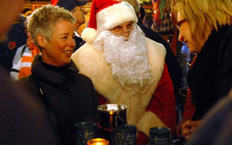 St. Nick chats with visitors at the Christmas market at Aachen, Germany, as they enjoy a mug of hot, mulled wine.