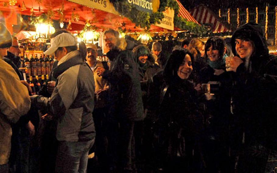 Nuremberg Christkindlesmarkt visitors enjoy a mug of Glühwein, the hot mulled wine that the season is famous for.
