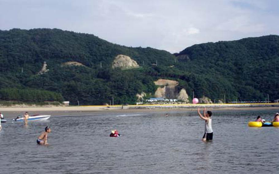 Beachgoers relax at Seopori Beach on Deokjeokdo. The beach, the most popular on the small island, includes concessions and small pine forest.