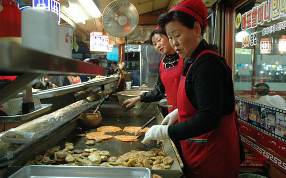 The pancakes are fried to order just outside the dining room. Here, the cooks are making jeon with red pepper paste, which goes well with beer or dong dong ju, a traditional Korean rice wine.