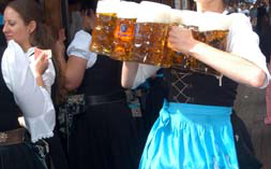 A server rushes with several liters of beer to thirsty customers at the Löwenbräu tent. One liter of beer costs about 8.60 euros.