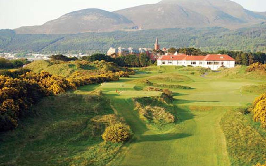 A view of Northern Ireland's Royal County Down Golf Club, clubhouse in foreground, looking toward the Mourne Mountains and the Slieve Donard Hotel (with steeple).