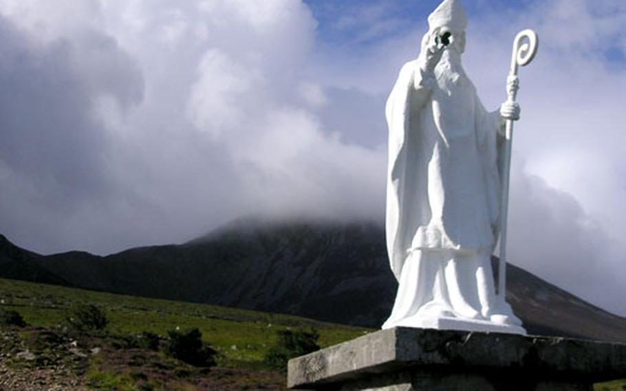 A statue of St. Patrick stands in front of Crough Patrick, Ireland's holy mountain. The top is hidden by clouds.