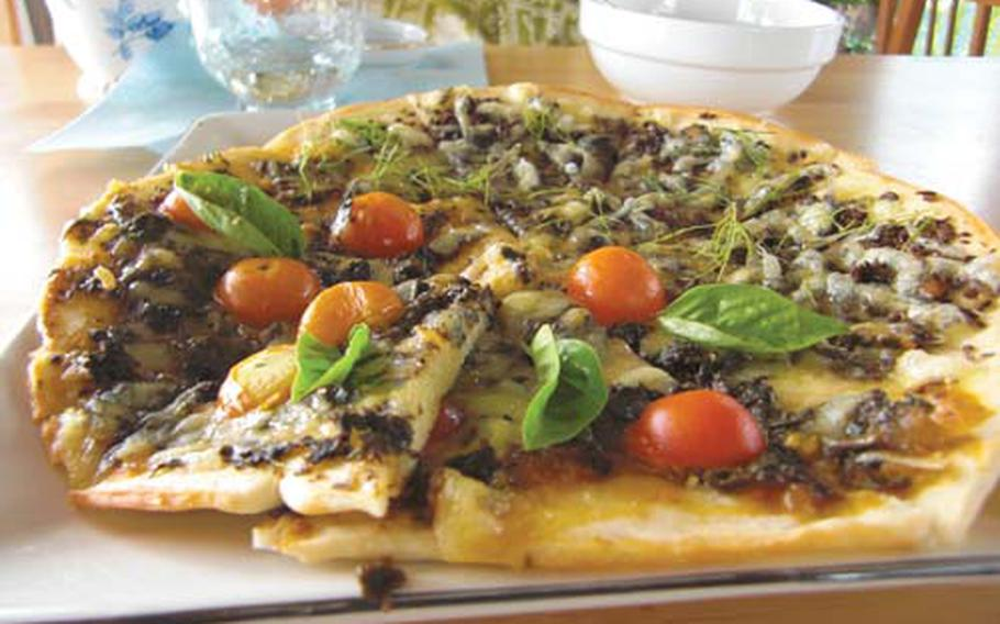 Fresh dill, basil and tomatoes garnish a pizza at the coffee shop. More than 200 kinds of herbs are grown at the farm's herb garden.