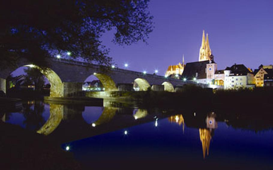 """The illuminated Regensburg cathedral is reflected in what is famously known as the """"Blue Danube"""" at twilight. In the foreground is the historic Steinerne Brücke, or Stone Bridge."""