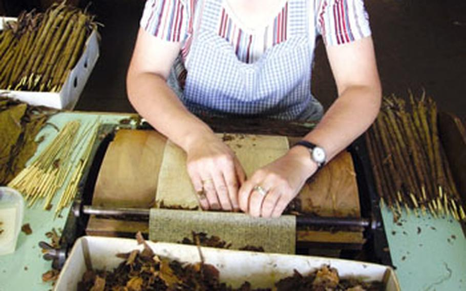 A Wolf und Ruhland employee rolls one of the 17 different types of cigars produced by the company.