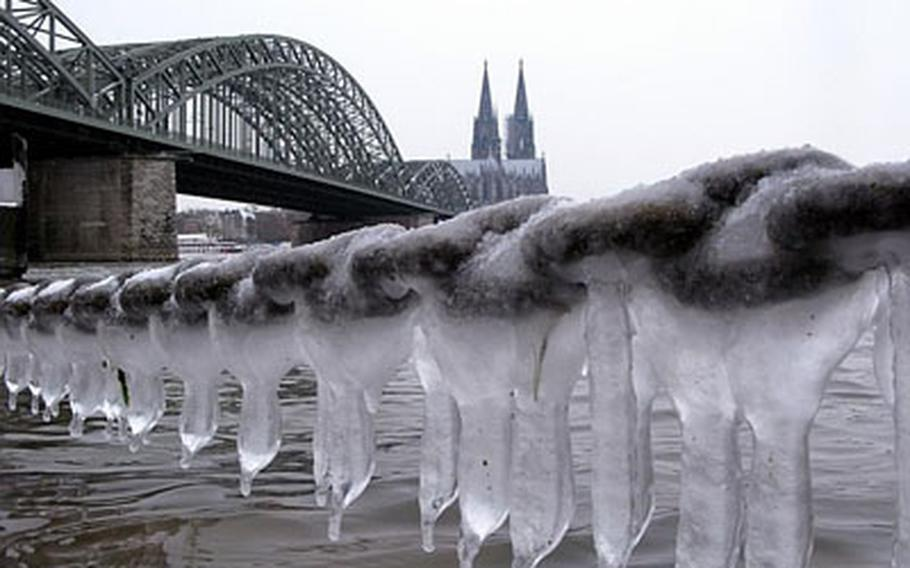 Icicles hang from chain links over the Rhine river, with the Cologne cathedral in the background, in Cologne, Germany.