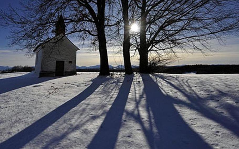 Trees cast shadows next to a chapel near Feldkirchen, southern Germany.