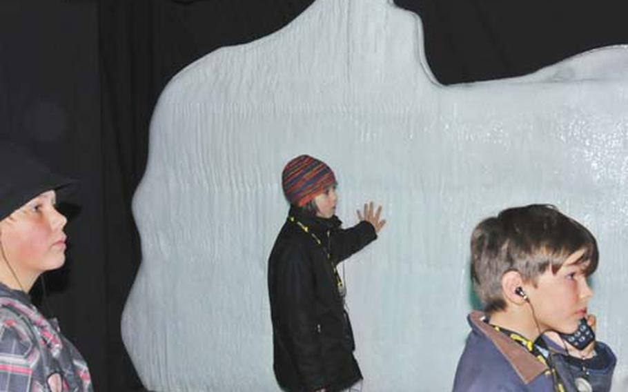 A group of young visitors listens to a lecture about icebergs in front of an artificial iceberg at the Titanic exhibit. As they touch the iceberg, they learn about the icy temperatures of the sea at the time of the disaster.