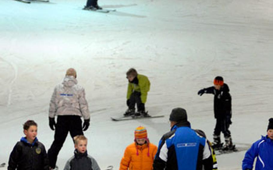 Student skiers listen to an instructor as others work their way down the 8,200 square foot kiddy piste at Snow Valley.