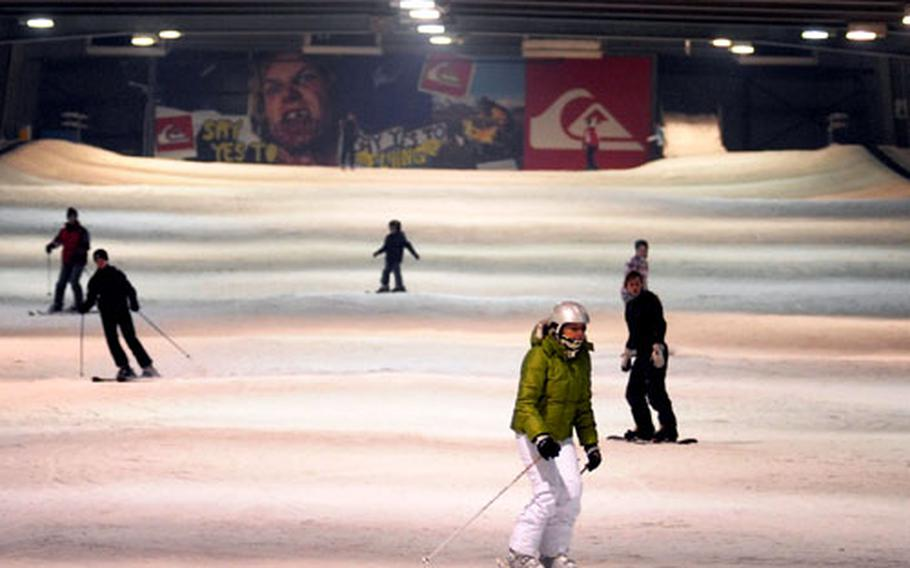 Skiers and snowboarders traverse the main ski area at Snow Valley indoor resort.