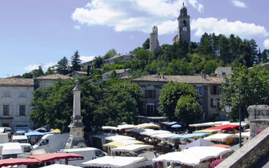 An ancient church dominates a hilltop in Reillanne, France. The Sunday market takes place in the square below.