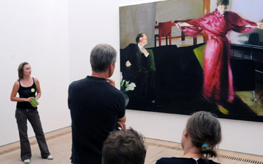 """A guide talks about Eric Fischl's masterpiece """"Living room no. 3,"""" one of the many highlights of the museum."""