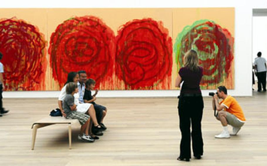 """A photographer takes souvenir shots of a group of visitors inside a room in the Museum Brandhorst featuring American artist Cy Twombly's series of paintings titled """"Roses."""""""